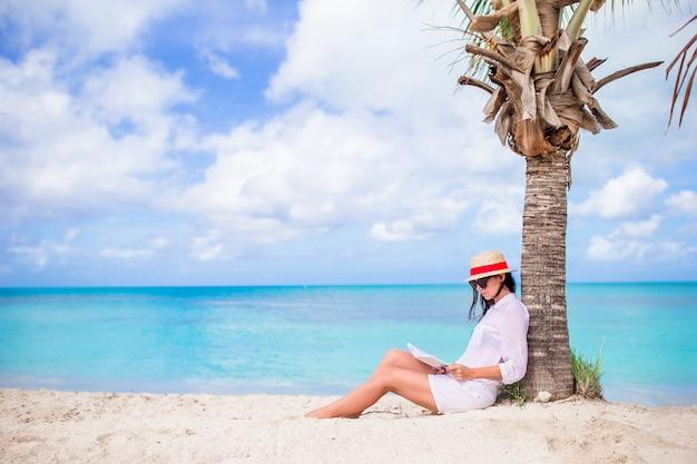 Buch der jungen frau lesewährend des tropischen weißen strandes Premium Fotos