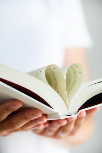Buch mit geöffneten seiten und form des herzens in mädchenhänden. Premium Fotos
