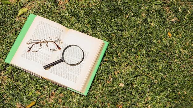 Buch mit optischen geräten auf grünem gras Kostenlose Fotos