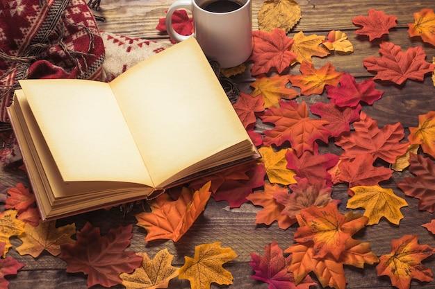 Buch und decke in der nähe von kaffee auf den blättern Kostenlose Fotos