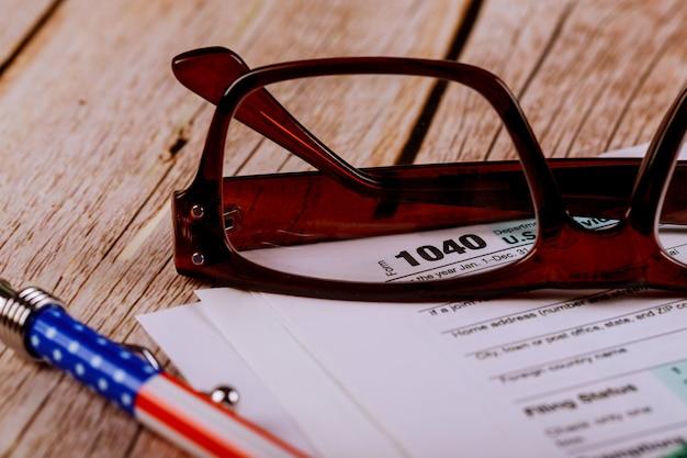 Buchhalter büro dokumentiert steuerformular fokus auf 1040, geringe schärfentiefe mit stift, brille Premium Fotos
