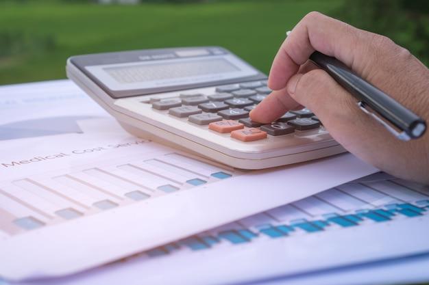 Buchhalterhände berechnen das finanzberichtsdiagramm und zählen auf taschenrechner Premium Fotos