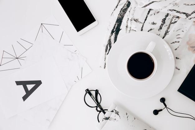 Buchstabe a; brille; smartphone; kopfhörer; kaffeetasse auf weißem schreibtisch Kostenlose Fotos
