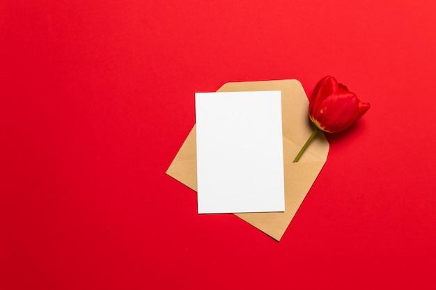 Buchstabe, umschlag im eco papier und rote tulpe auf hintergrund. valentine Premium Fotos