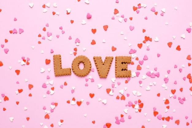 Buchstabeplätzchen ich liebe dich mit den rosa und roten herzen auf rosa Premium Fotos