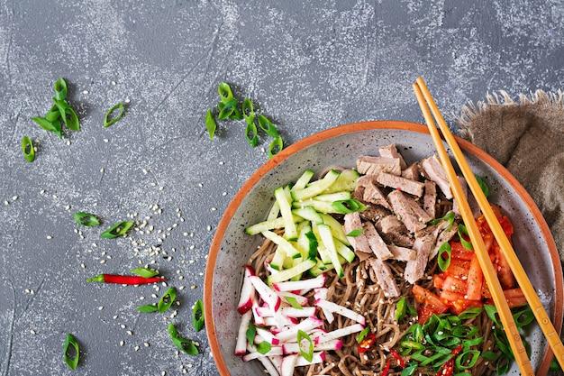 Buchweizennudeln mit rindfleisch, eiern und gemüse. koreanisches essen. buchweizennudelsuppe. ansicht von oben. flach liegen Premium Fotos