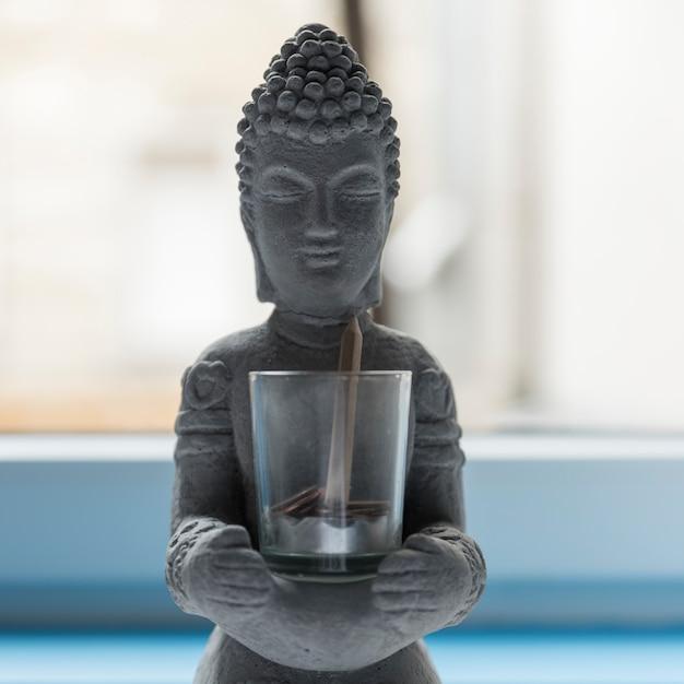 Buddha aus zement mit glas mit münzen und einem bleistift Premium Fotos