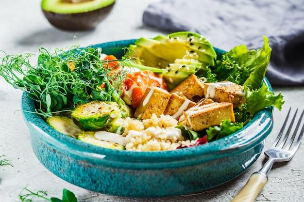 Buddha-schale mit quinoa, tofu, avocado, süßkartoffel, rosenkohl und tahini-dressing Premium Fotos