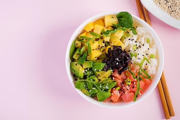 Buddha schüssel mit reis, mango, avocado und lachs. gesundes lebensmittelkonzept. Premium Fotos