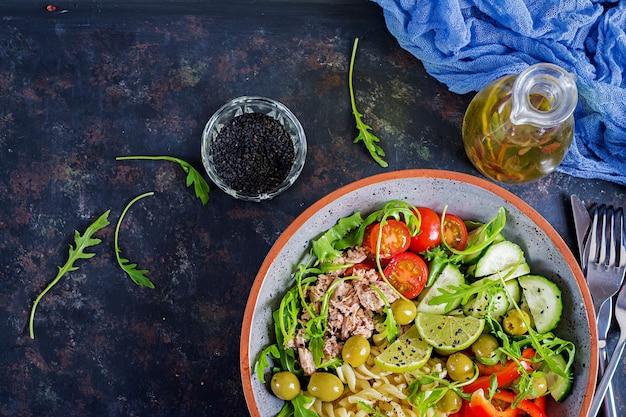 Buddha schüssel. nudelsalat mit thunfisch, tomaten, oliven, gurke, gemüsepaprika und arugula auf rustikalem hintergrund. ansicht von oben Premium Fotos