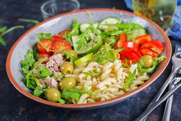 Buddha schüssel. nudelsalat mit thunfisch, tomaten, oliven, gurke, gemüsepaprika und arugula auf rustikalem hintergrund Premium Fotos