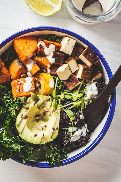 Buddha-schüsselsalat mit schwarzem reis, avocado, tofu, süßkartoffel, kohl und tahini-dressing Premium Fotos