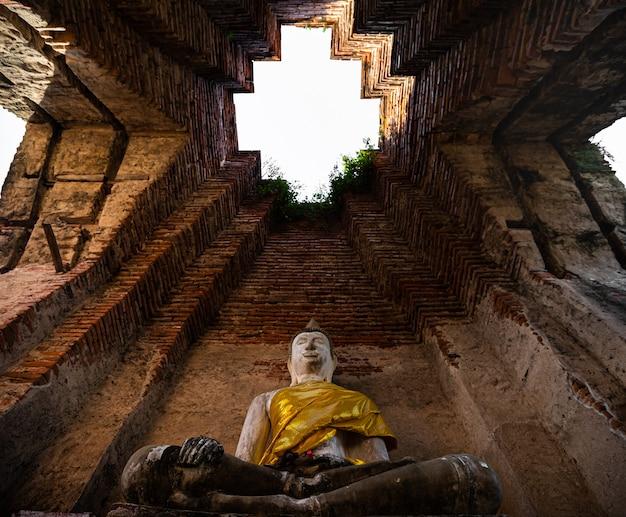 Buddha-statue, die auf sockeln mit alter antiker backsteinmauer hinter dem tempel mit ruinen von ayutthaya thailand sitzt Premium Fotos