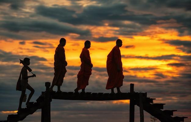 Buddhistische mönche auf den traditionellen almosen des täglichen morgens, die in thailand geben. Premium Fotos