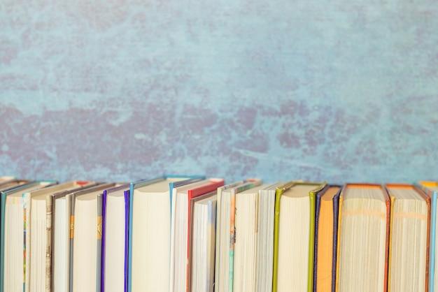 Bücher auf bücherregal, blauer hintergrund, weinlese getont. bildung, zurück zum schulthema. Premium Fotos