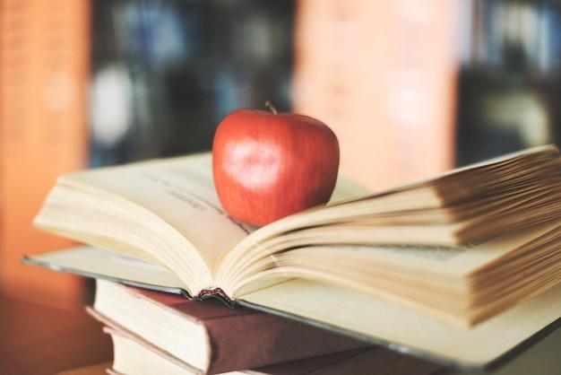 Bücher auf dem tisch in der bibliothek - bildung, die alten bücherstapel auf holzschreibtisch und verschwommenem bücherregalraumhintergrund mit apfel auf offenem buch lernt, zurück zum schulkonzept Premium Fotos