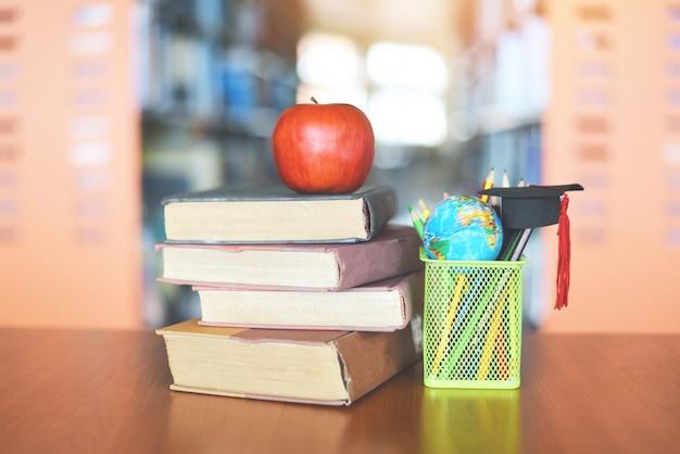 Bücher auf dem tisch in der bibliothek - bildung, die alten bücherstapel und abschlusskappe auf einem federmäppchen mit erdkugelmodell auf holzschreibtisch und verschwommenem bücherregalraum mit apfel auf buch lernt Premium Fotos