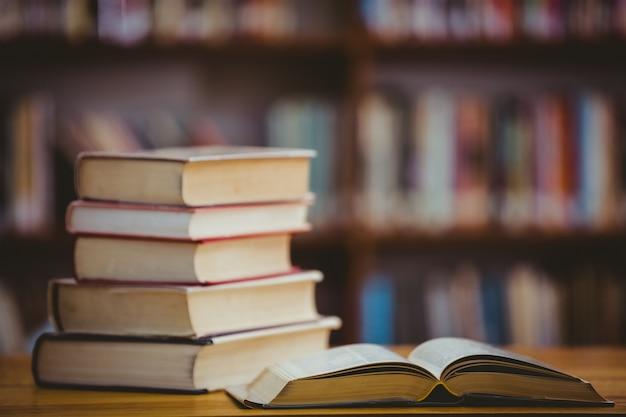 Bücher auf schreibtisch in der bibliothek Premium Fotos