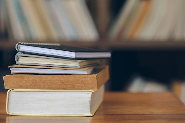 Bücher gestapelt auf dem alten holztisch in der bibliothek. Premium Fotos