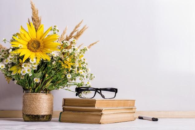 Bücher, gläser, markierungen und ein blumenstrauß in einer vase auf weißem brett Premium Fotos