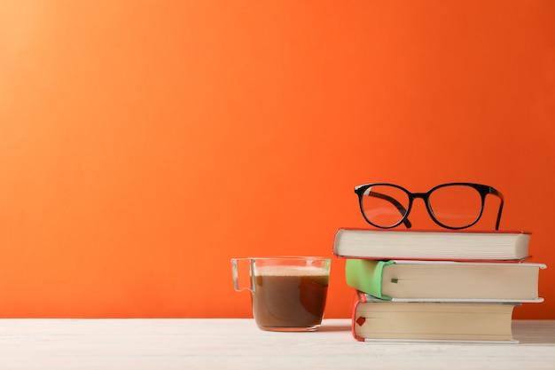 Bücher, gläser und eine tasse kaffee gegen orangefarbenen raum, platz für text Premium Fotos