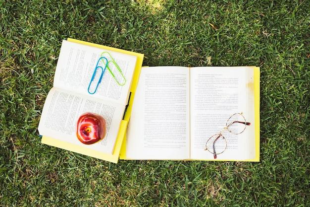 Bücher mit gläsern und apfel auf gras Kostenlose Fotos