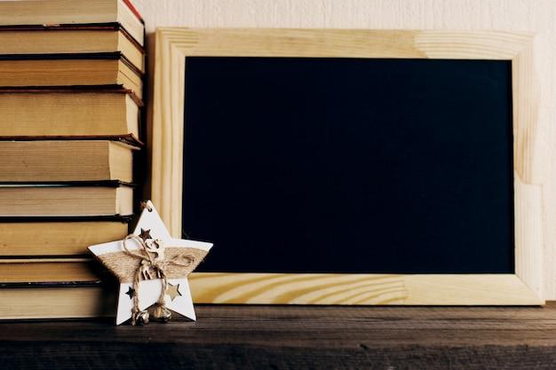Bücher und ein weihnachtsbaum mit kegeln und eine sterndekoration auf einem alten hölzernen regal. Premium Fotos