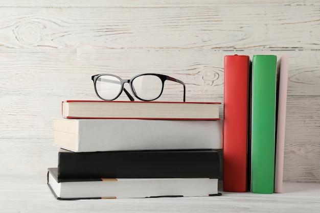 Bücher und gläser gegen rustikalen hölzernen hintergrund, platz für text Premium Fotos