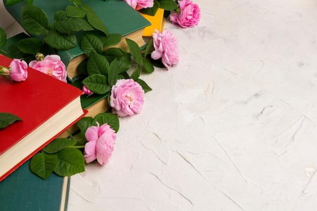 Bücher und rosen auf einer hellen steinoberfläche. konzeptbücher über liebe und romantische romane Premium Fotos