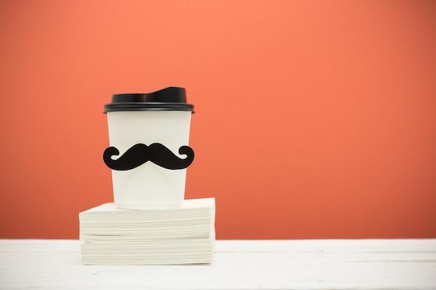 Bücher und schale mit dem schnurrbart auf holztisch über orange hintergrund. hipster-stil. Premium Fotos