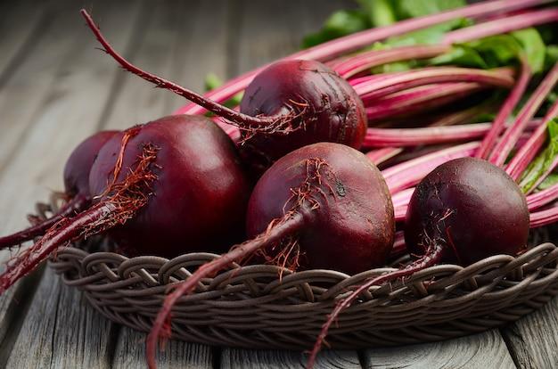 Bündel frische organische rote rüben auf rustikalem holztisch. Premium Fotos
