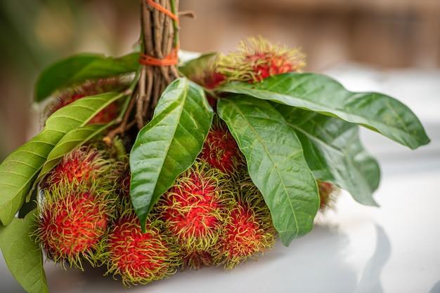 Bündel frische reife rambutan-früchte mit grünen blättern. Premium Fotos