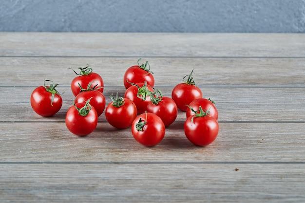 Bündel frische saftige tomaten auf holztisch. Kostenlose Fotos