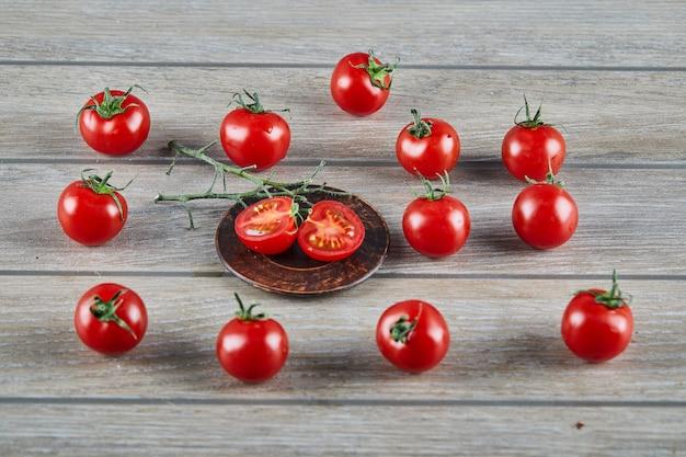 Bündel frische saftige tomaten und tomatenscheiben auf holztisch. Kostenlose Fotos