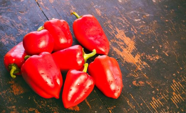 Bündel frischer reifer roter paprika auf einer alten schwarzen holzgrungeoberfläche Premium Fotos