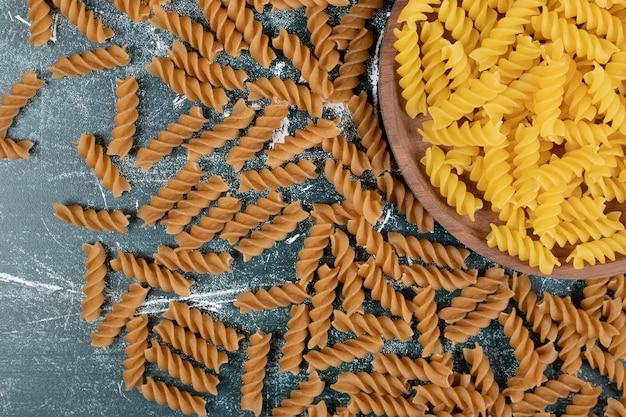 Bündel gelbe und braune fusilli-nudeln auf blauem hintergrund. hochwertiges foto Kostenlose Fotos