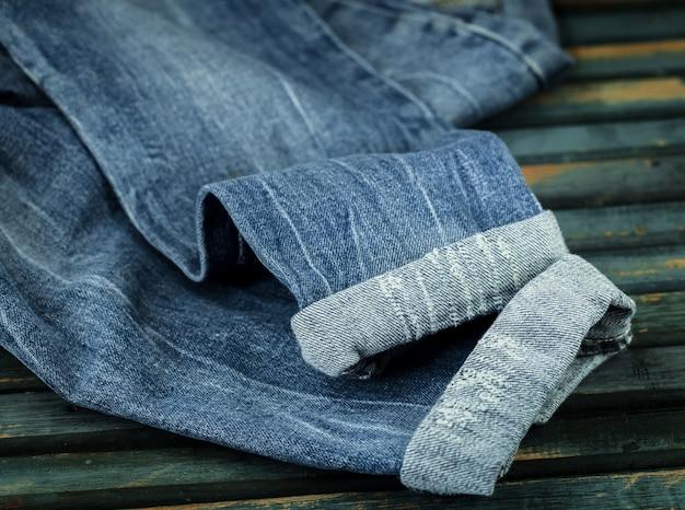 Bündel jeans auf einem hölzernen hintergrund verstreute jeans, nahaufnahme, modische kleidung Kostenlose Fotos