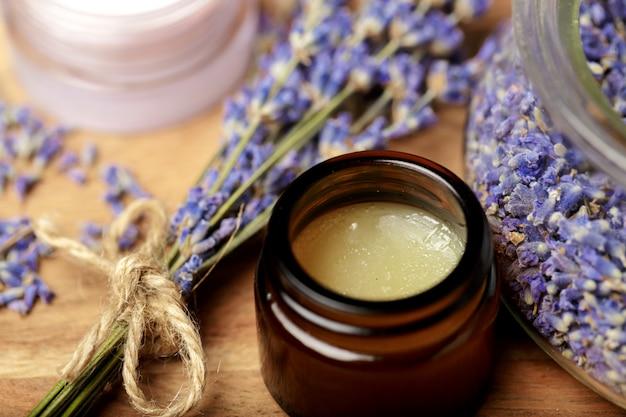 Bündel lavendel und kosmetischer topf auf einem holztisch Premium Fotos