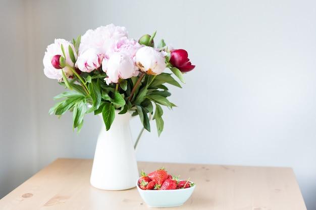 Bündel rosa pfingstrosen in vase und erdbeere auf dem holztisch. Premium Fotos