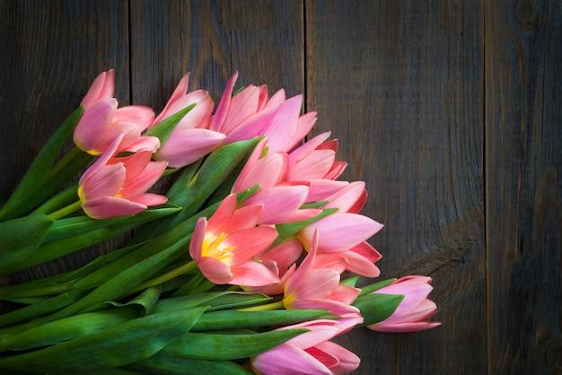 Bündel rosa tulpen auf hölzernem dunklem hintergrund Premium Fotos