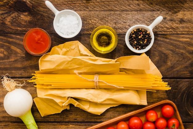 Bündel spaghettis nahe gewürzen und gemüse Kostenlose Fotos