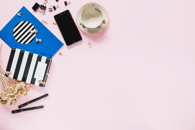 Bündel weiße blumen mit briefpapier; handy und leere tasse auf rosa hintergrund Kostenlose Fotos