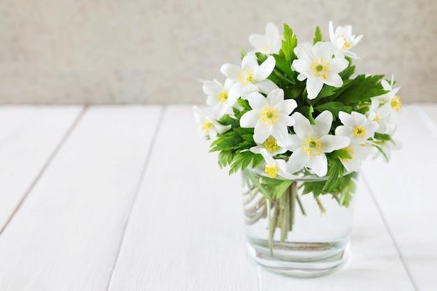 Bündel weißer frühling blüht in einem glas Premium Fotos