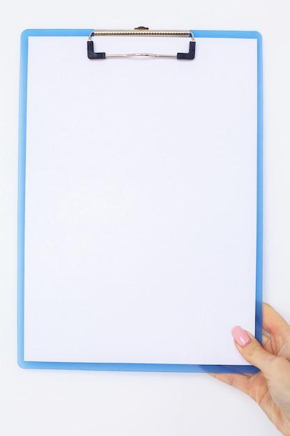 Büro-hand, die einen ordner mit einem weißen farbpapier auf dem hintergrund der weißen tabelle hält Premium Fotos