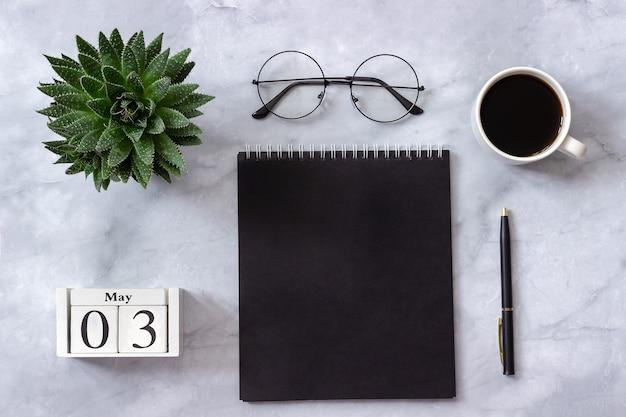 Büro oder heimtisch. kalender 3. mai schwarzer notizblock, kaffee, succulent, gläser auf marmorhintergrund Premium Fotos