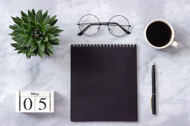 Büro oder heimtisch, kalender 5. mai. schwarzer notizblock, kaffee, succulent, gläser auf marmor Premium Fotos