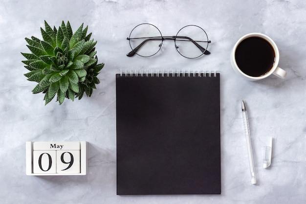 Büro oder zu hause tisch, kalender 9. mai. notizblock, kaffee, succulent, gläser konzept stilvollen arbeitsplatz Premium Fotos