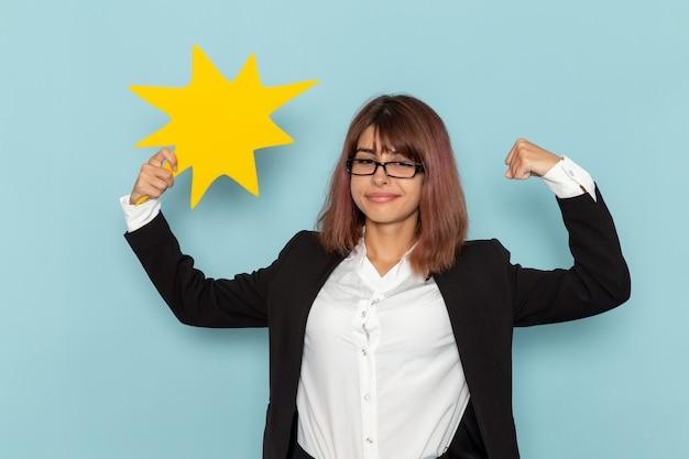 Büroangestellte der vorderansicht, die gelbes zeichen hält und auf der blauen oberfläche biegt Kostenlose Fotos