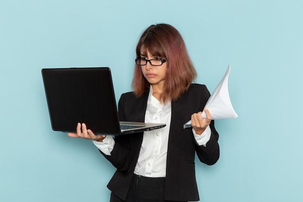 Büroangestellte der vorderansicht im strengen anzug unter verwendung des laptops und des haltens von papieren auf hellblauer oberfläche Kostenlose Fotos