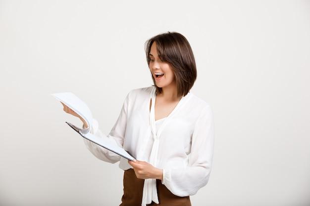 Büroangestellte, die dokumente liest Kostenlose Fotos